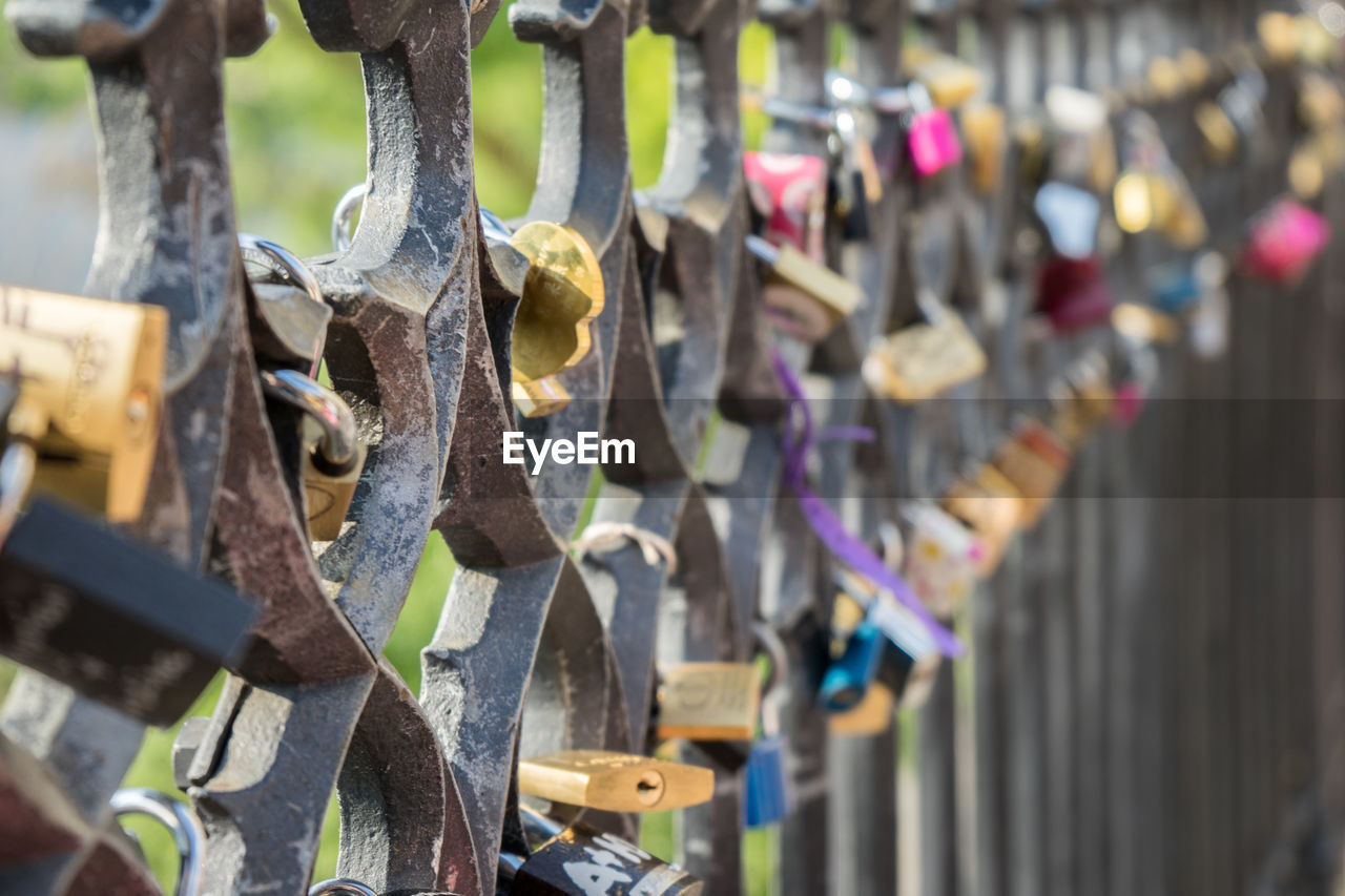 hanging, padlock, close-up, railing, fence, day, security, protection, lock, safety, barrier, boundary, metal, selective focus, no people, focus on foreground, love lock, large group of objects, outdoors, in a row