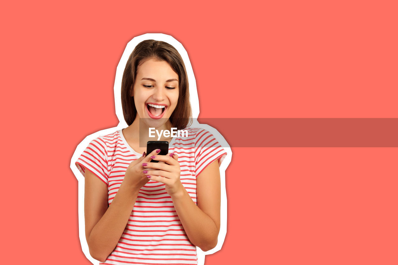Shocked young woman holding mobile phone cut out against coral background