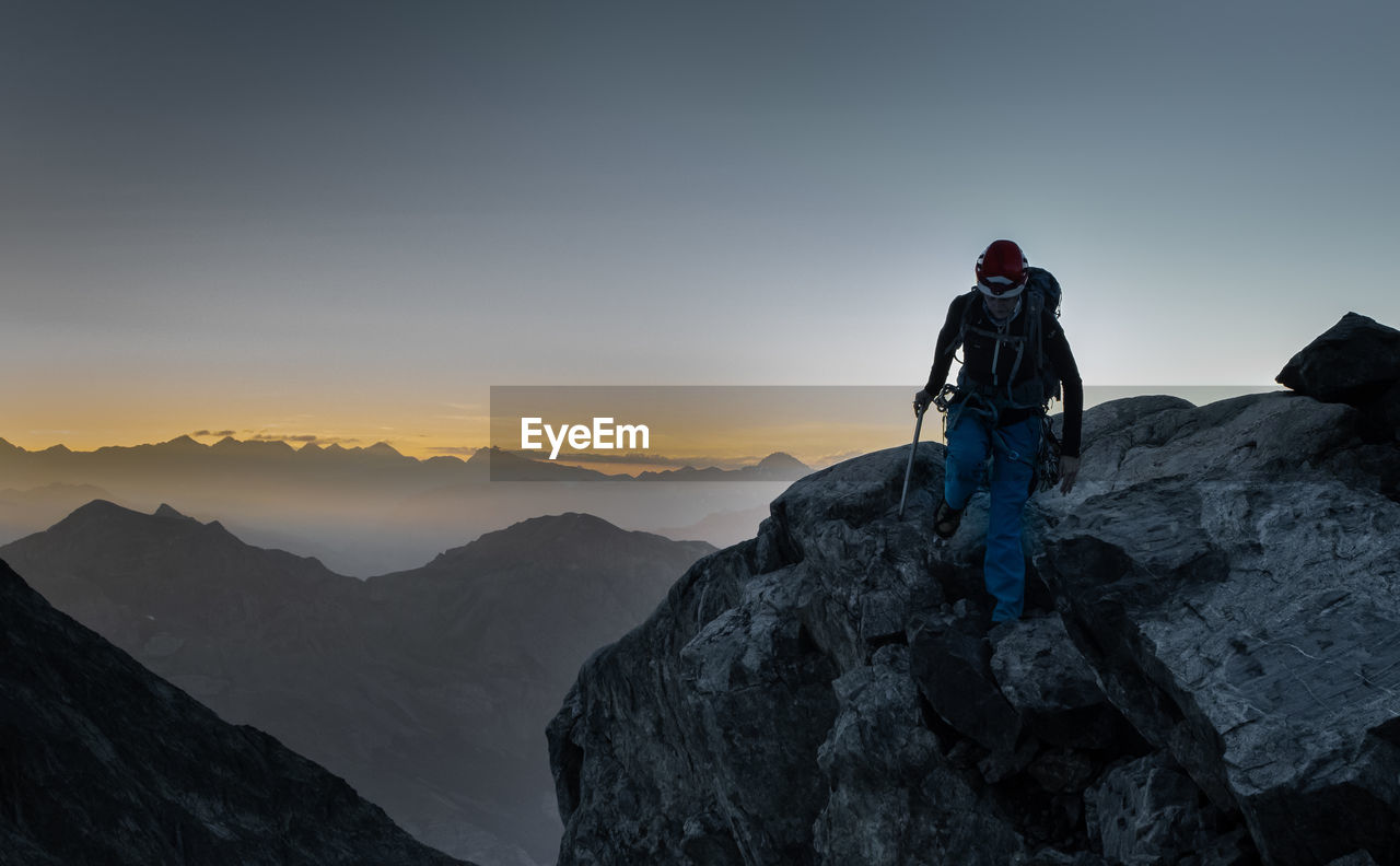 Hiker walking on rocky mountain during sunset