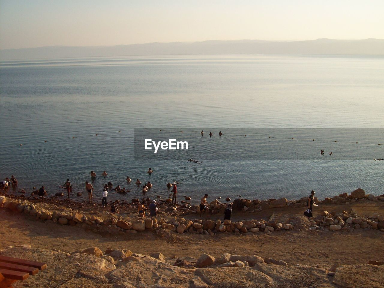 High angle view of people enjoying at rocky sea shore against clear sky