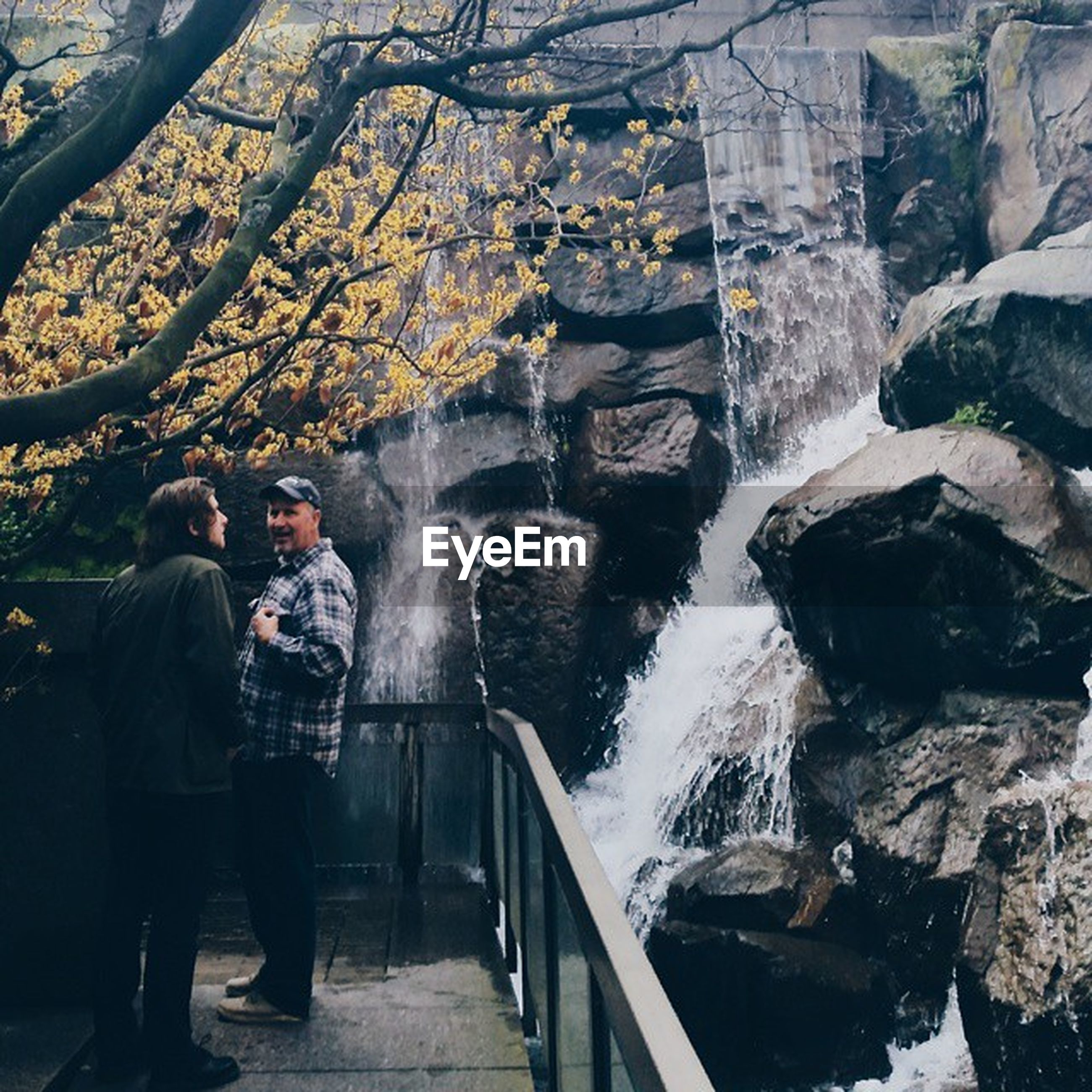 men, lifestyles, water, leisure activity, rock - object, rear view, full length, person, steps, standing, walking, built structure, motion, casual clothing, architecture, waterfall, nature
