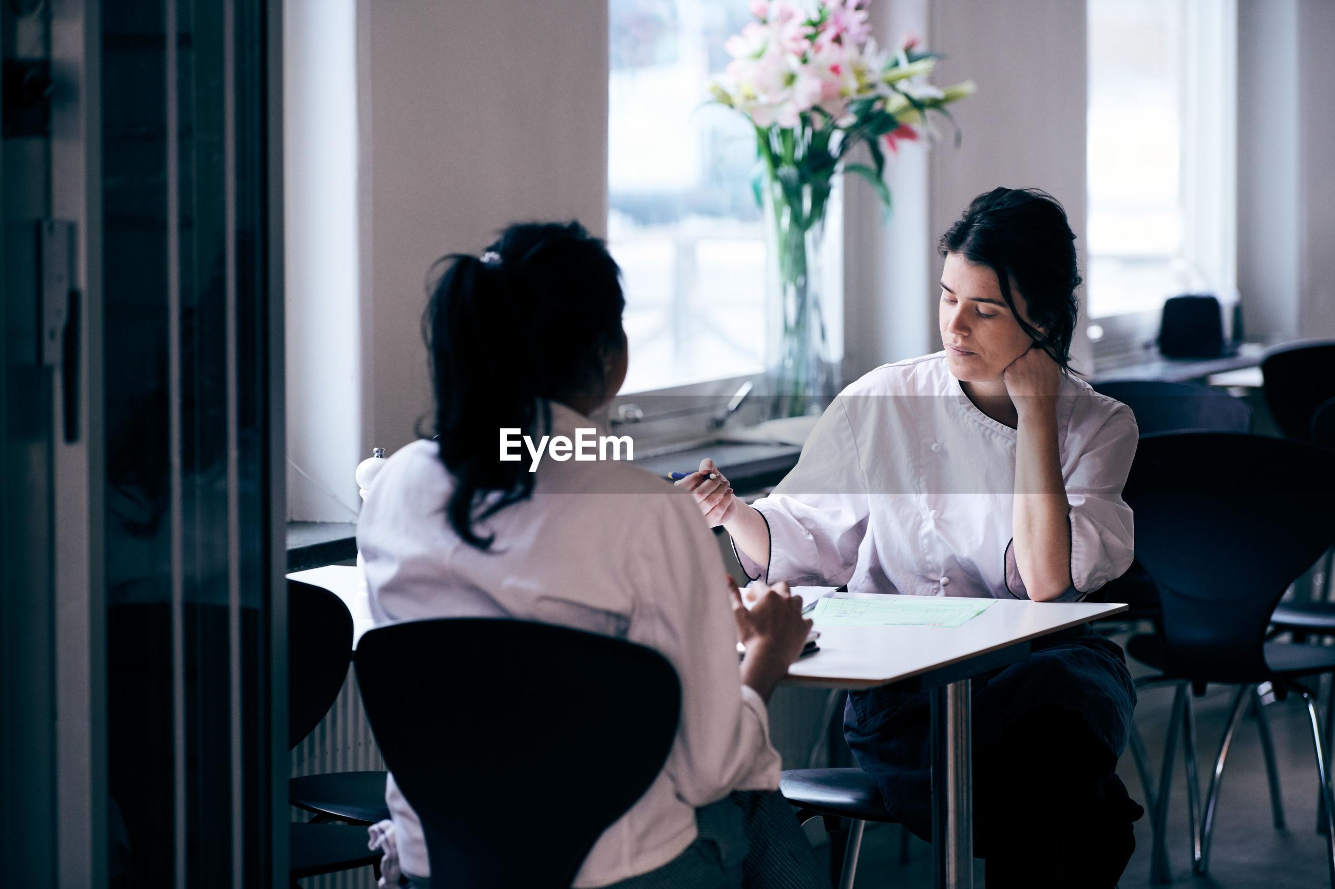 Chefs discussing menu in restaurant
