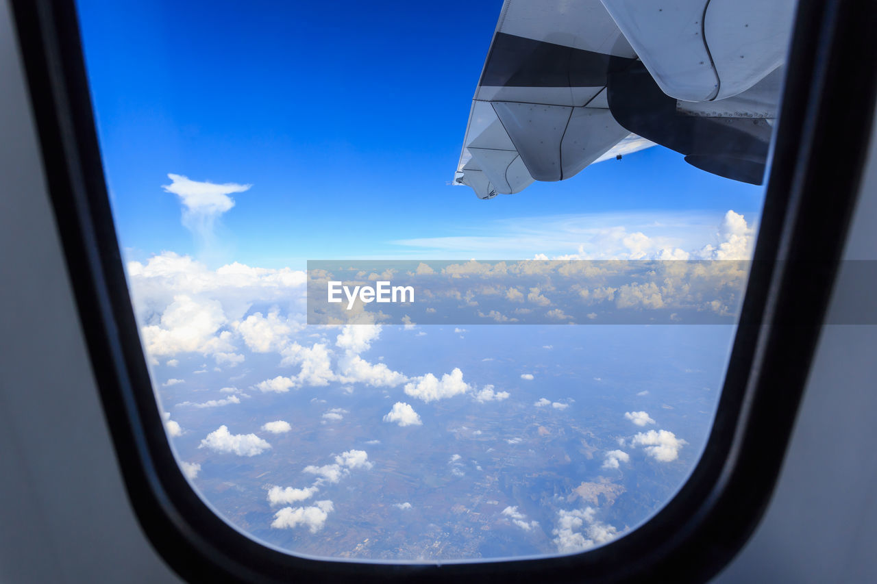 window, transparent, cloud - sky, glass - material, sky, mode of transportation, transportation, airplane, air vehicle, vehicle interior, flying, mid-air, nature, day, beauty in nature, aircraft wing, scenics - nature, travel, public transportation, blue, no people, outdoors, glass