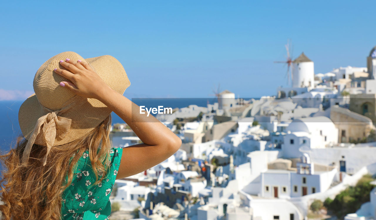 focus on foreground, architecture, hat, one person, building exterior, built structure, sky, nature, sunlight, day, lifestyles, city, leisure activity, women, rear view, building, real people, clear sky, clothing, outdoors, hairstyle