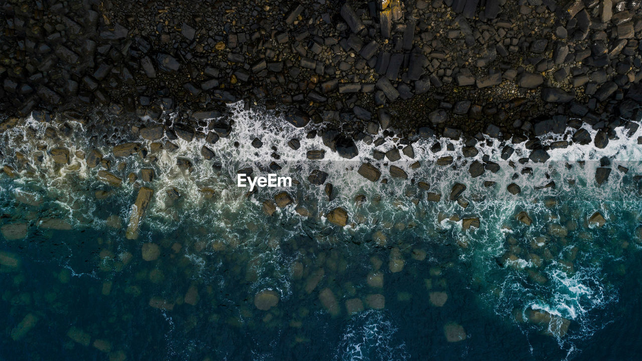 Aerial view of waves splashing on rocks