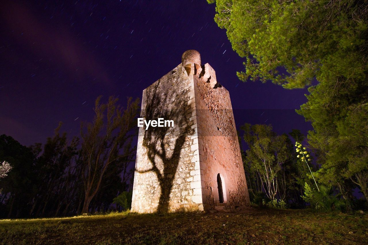 Low angle view of tower amidst trees against sky at night