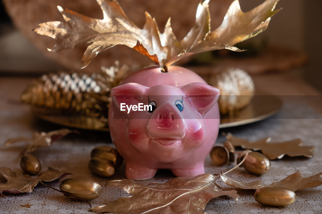 representation, table, still life, close-up, no people, indoors, pink color, art and craft, holiday, focus on foreground, selective focus, human representation, savings, celebration, piggy bank, investment, creativity, decoration, finance