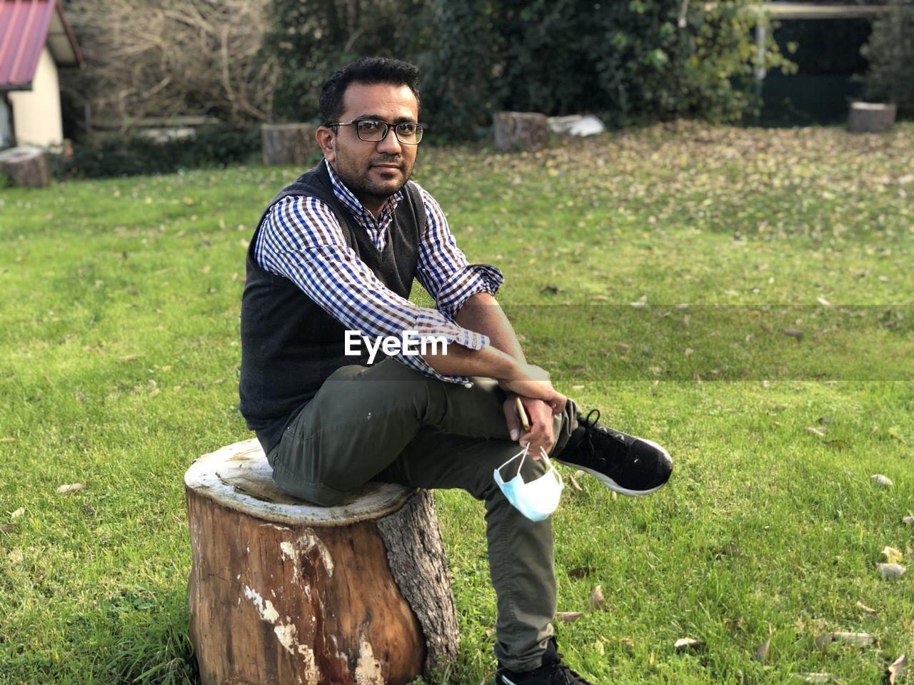 MAN SITTING ON FIELD
