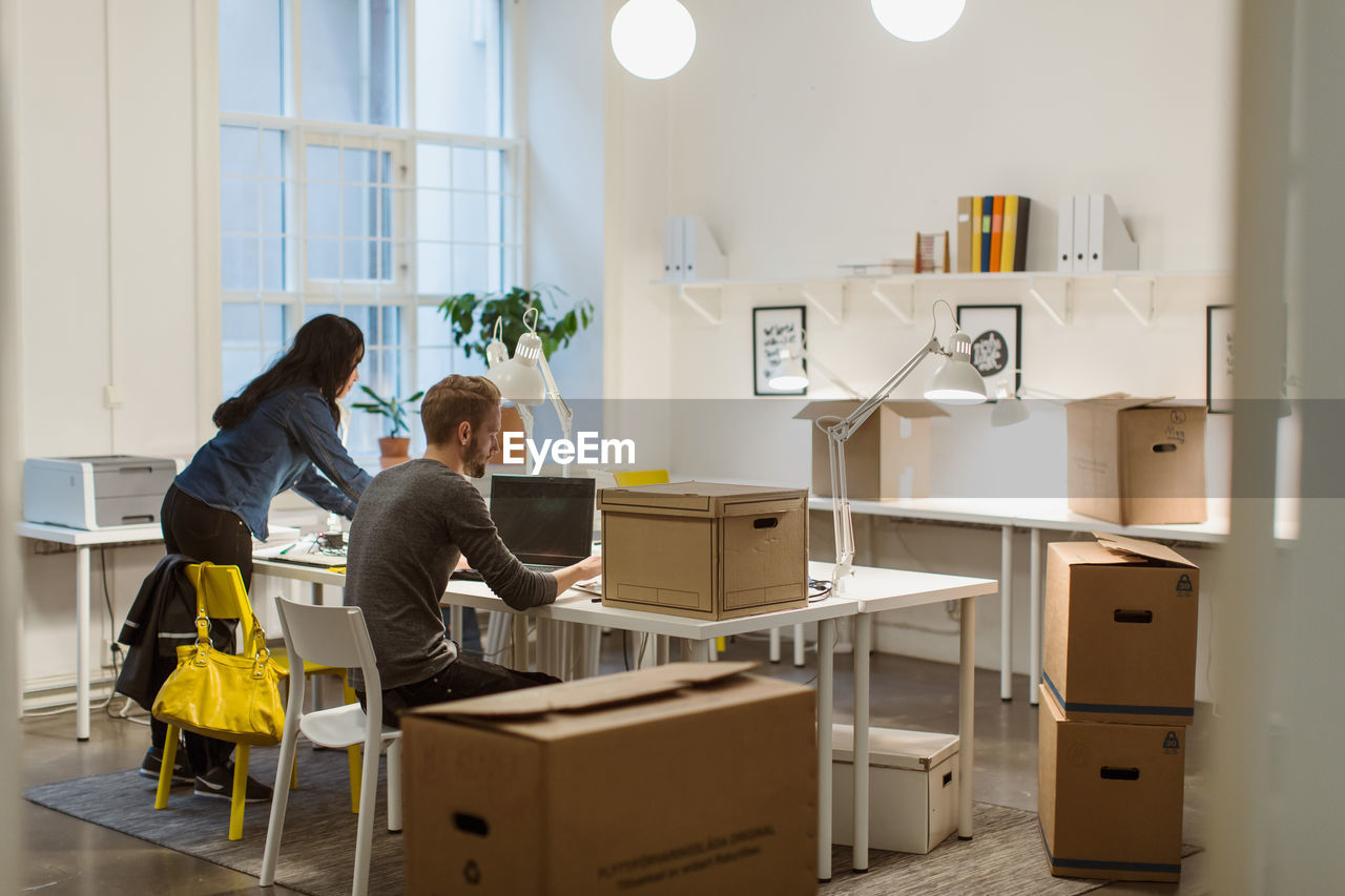 Business colleagues working at desk amidst cardboard boxes in illuminated creative office