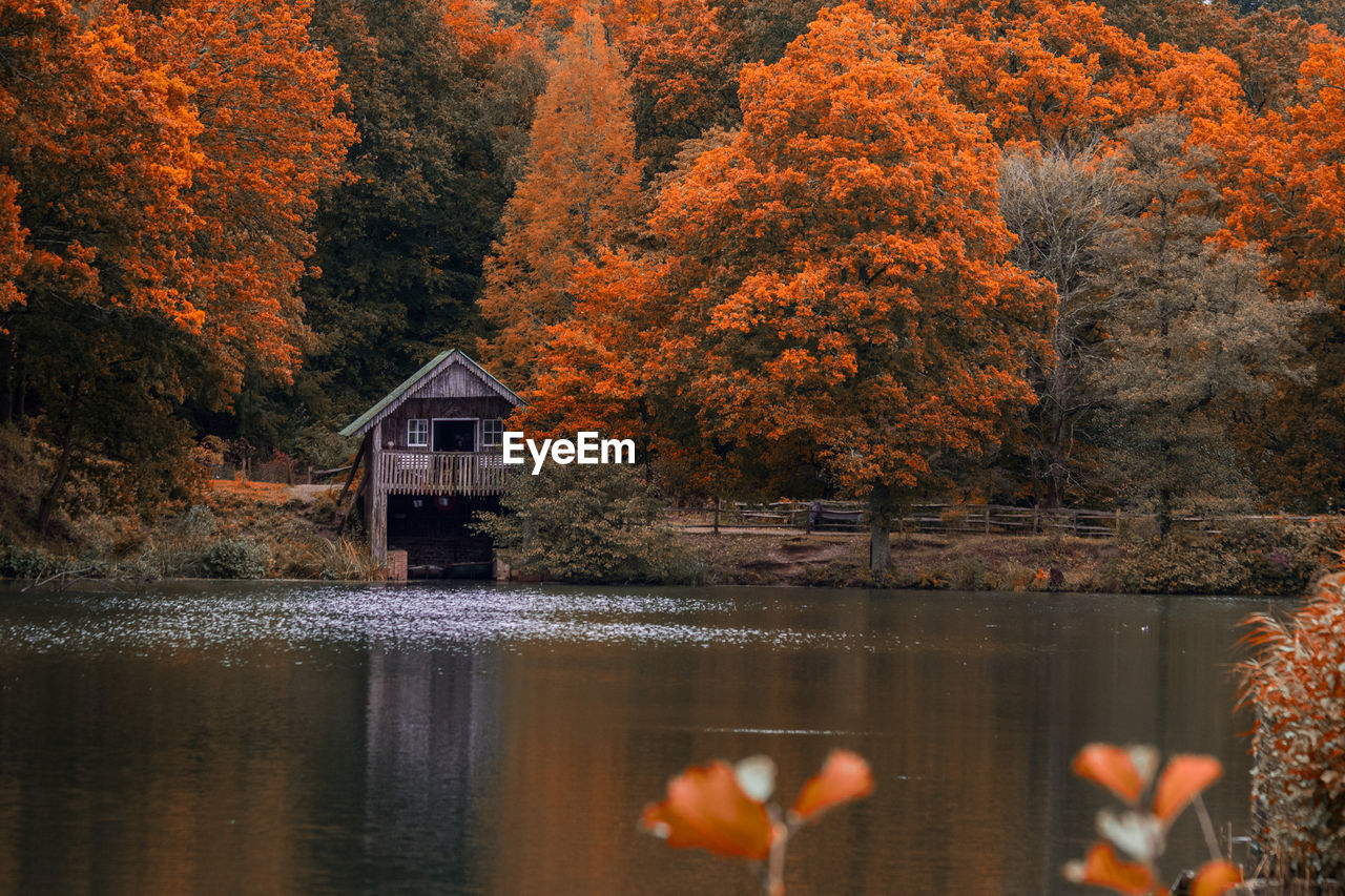 Scenic view of lake and boathouse in forest during autumn