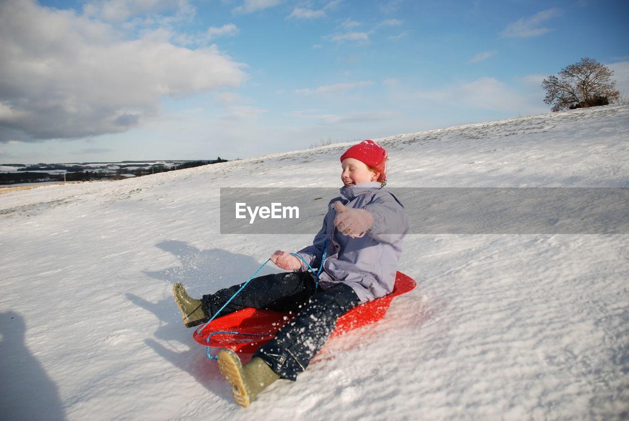 Smiling girl sledging on snow against sky