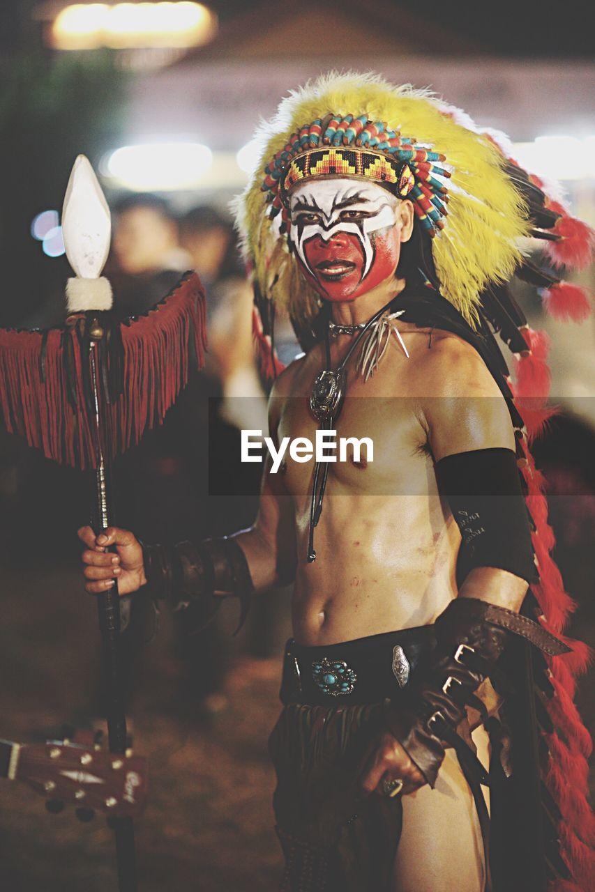 Man Looking Away While Wearing Tribal Costume At Night