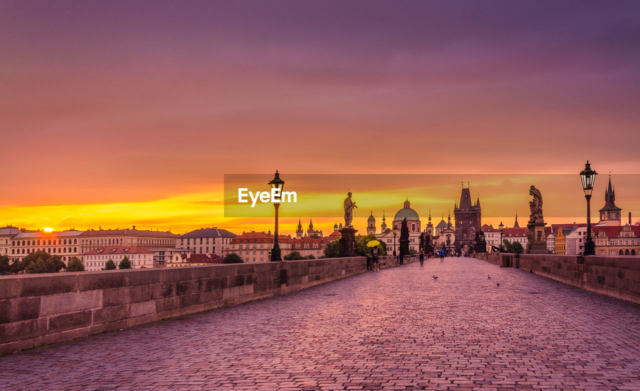 Charles bridge by historic buildings in city against orange sky during sunset