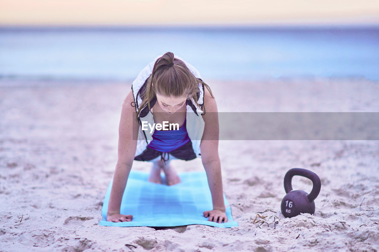 Young Woman Exercising On Exercise Mat At Beach