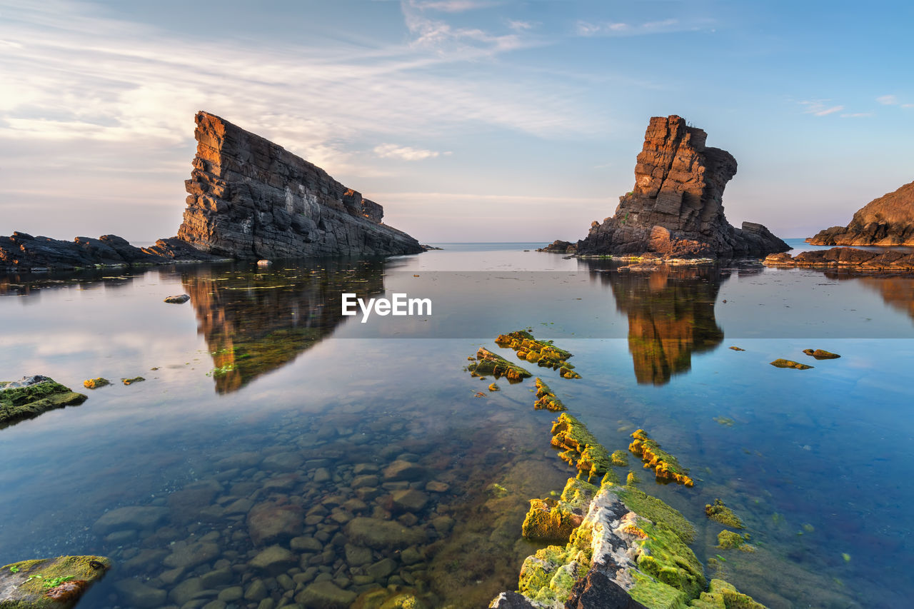 water, sky, tranquility, reflection, beauty in nature, scenics - nature, rock, tranquil scene, rock formation, no people, nature, rock - object, solid, sea, cloud - sky, non-urban scene, waterfront, sunset, idyllic, outdoors, stack rock, eroded