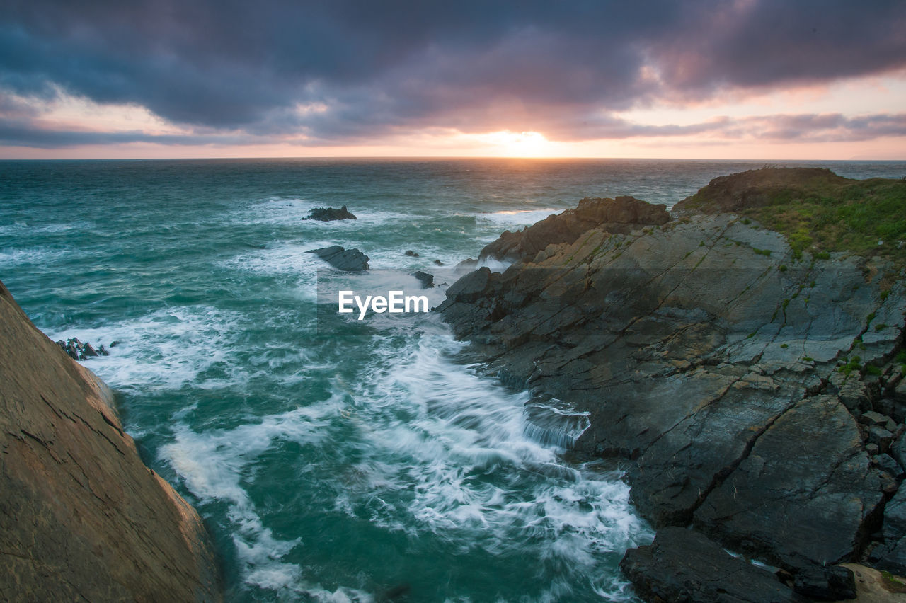 sea, water, beauty in nature, scenics - nature, sky, motion, horizon over water, beach, horizon, land, rock, cloud - sky, wave, rock - object, sunset, solid, nature, no people, aquatic sport, power in nature, outdoors, breaking, rocky coastline