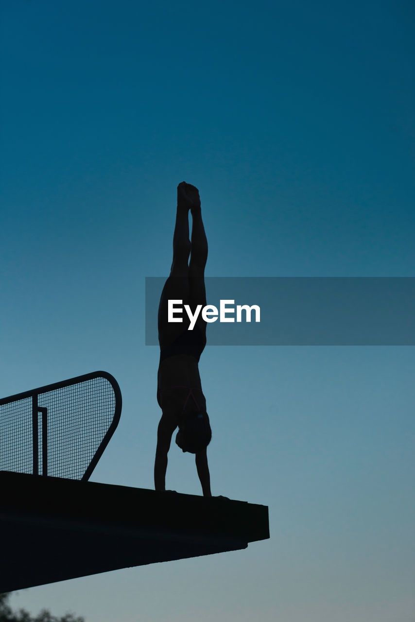 Low Angle View Of Silhouette Mid Adult Woman Doing Handstand On Diving Platform Against Clear Sky During Sunset