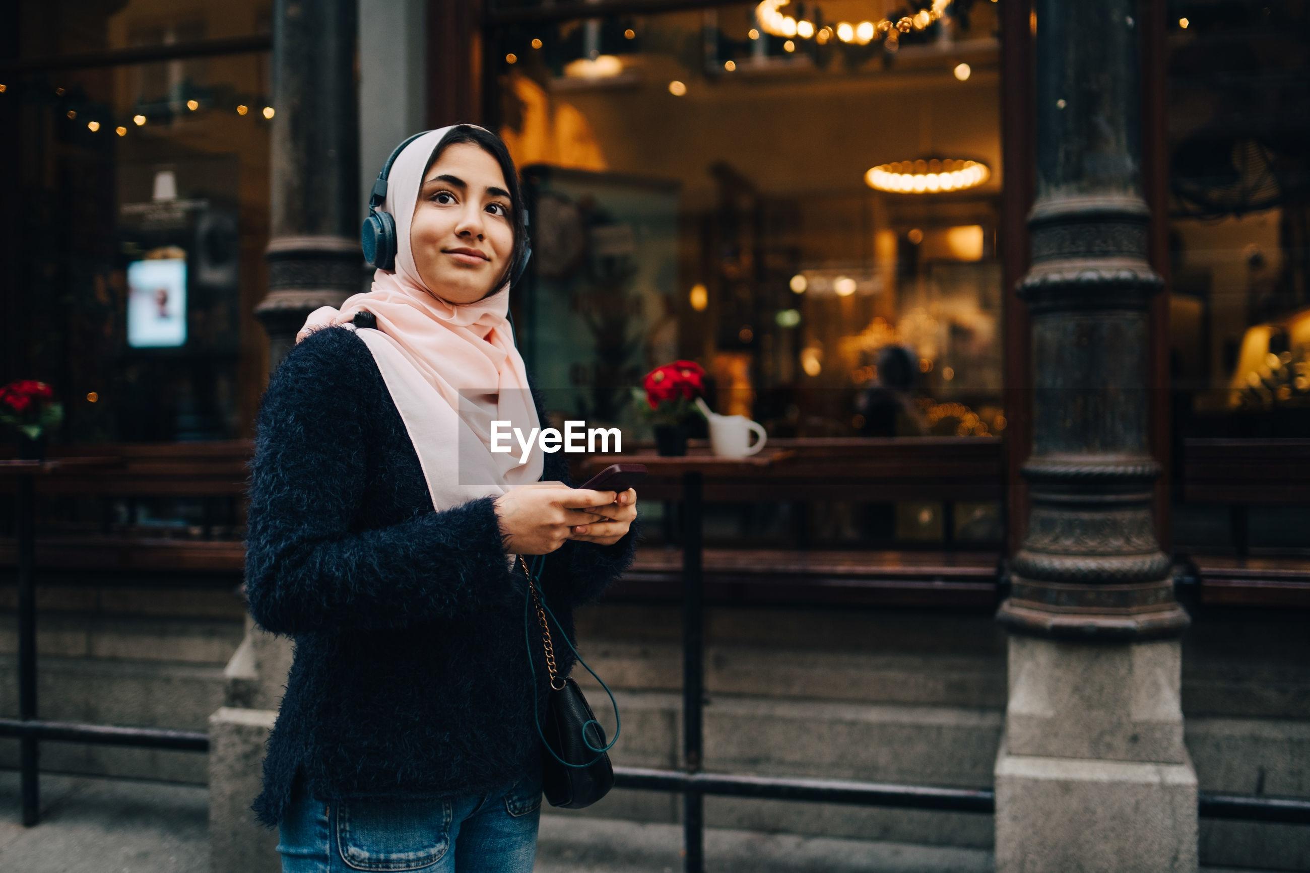 Teenage girl listening to headphones holding smart phone while looking away in city
