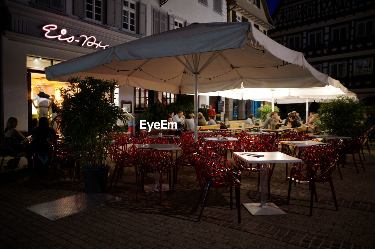 architecture, built structure, building exterior, food and drink, table, seat, chair, city, cafe, building, business, restaurant, sidewalk cafe, nature, incidental people, food, group of people, place setting, food and drink industry, outdoors, setting, dining