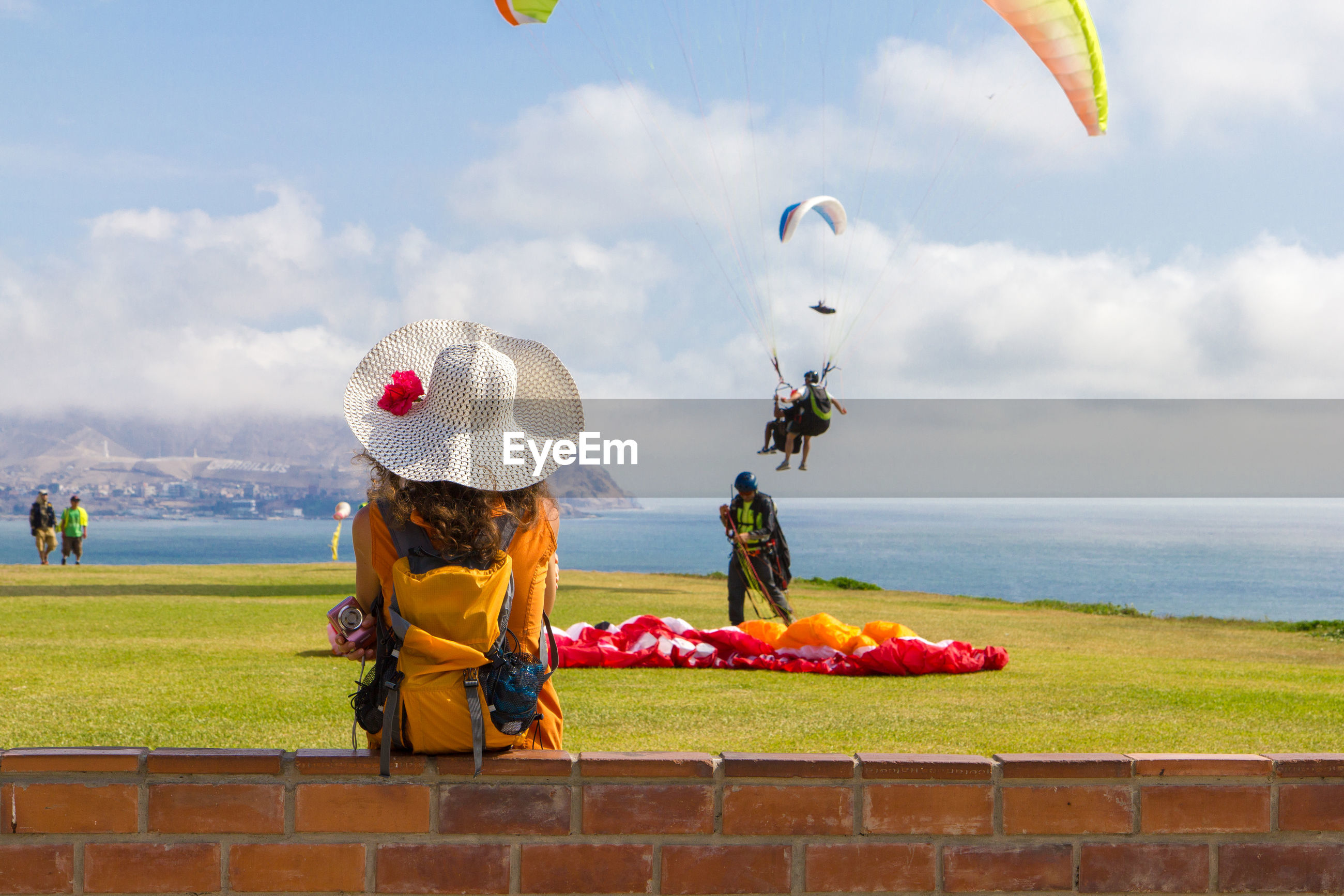 Paragliding on landscape against clouds