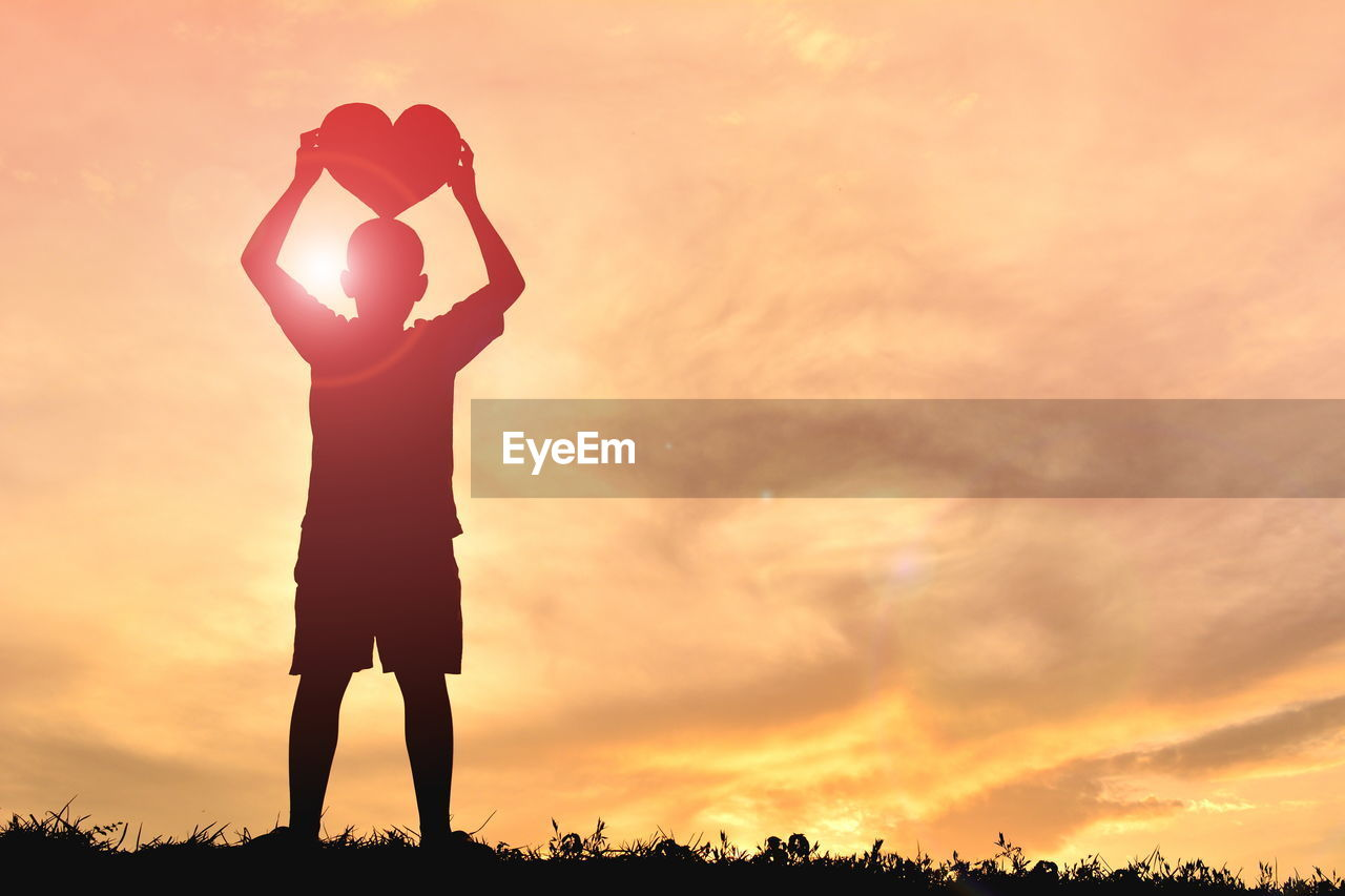 Silhouette boy holding heart shape on field against sky during sunset