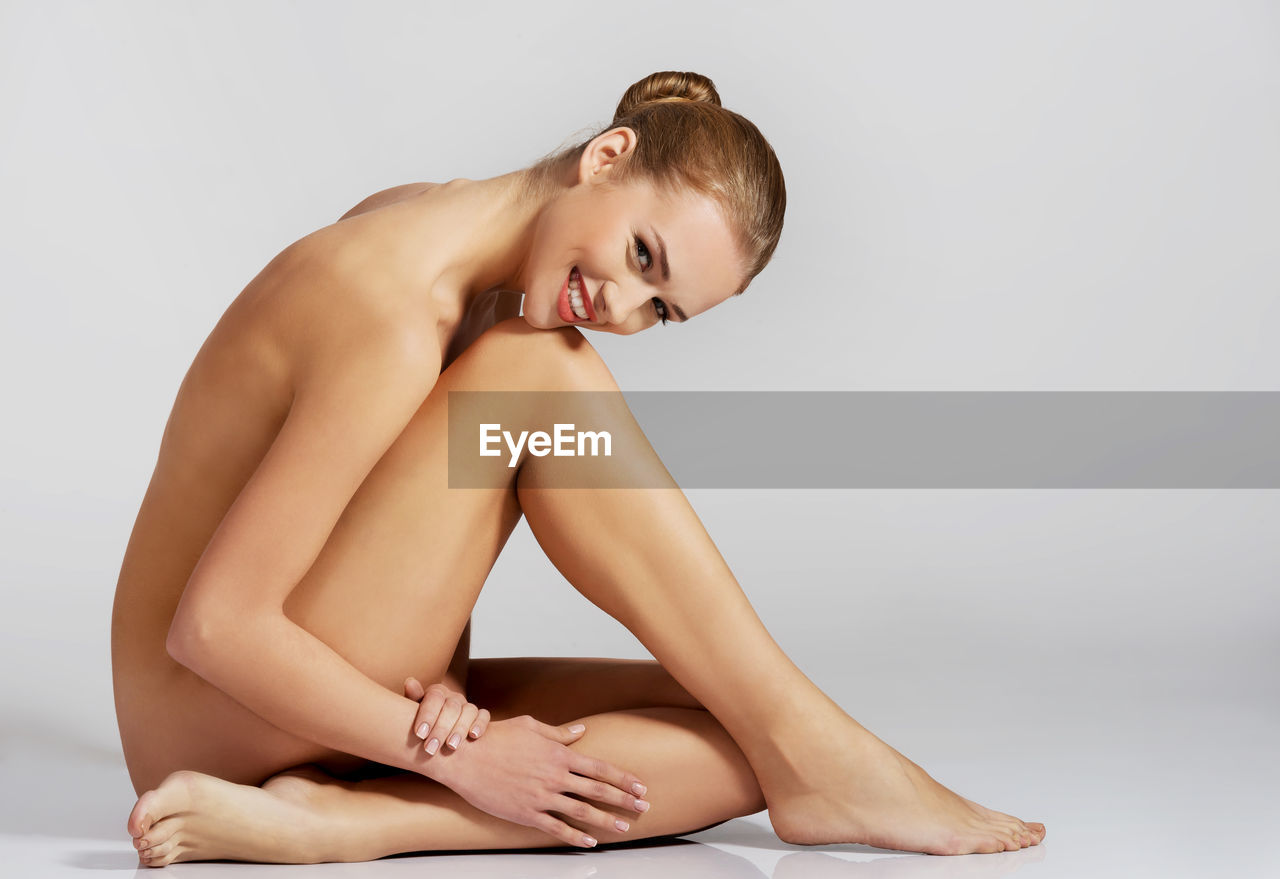 Side view portrait of naked young woman sitting against white background