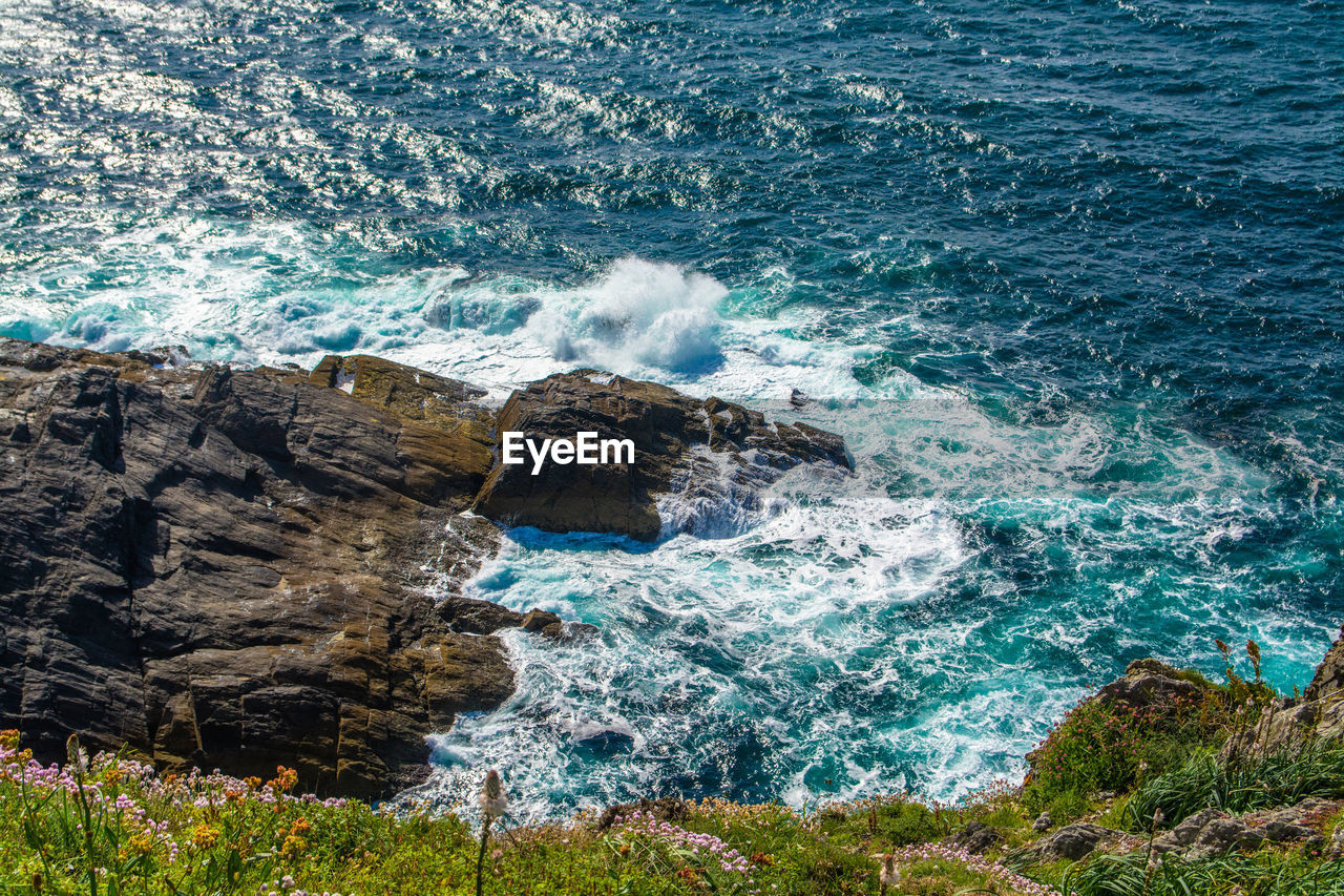 High angle view of sea waves rushing towards rock
