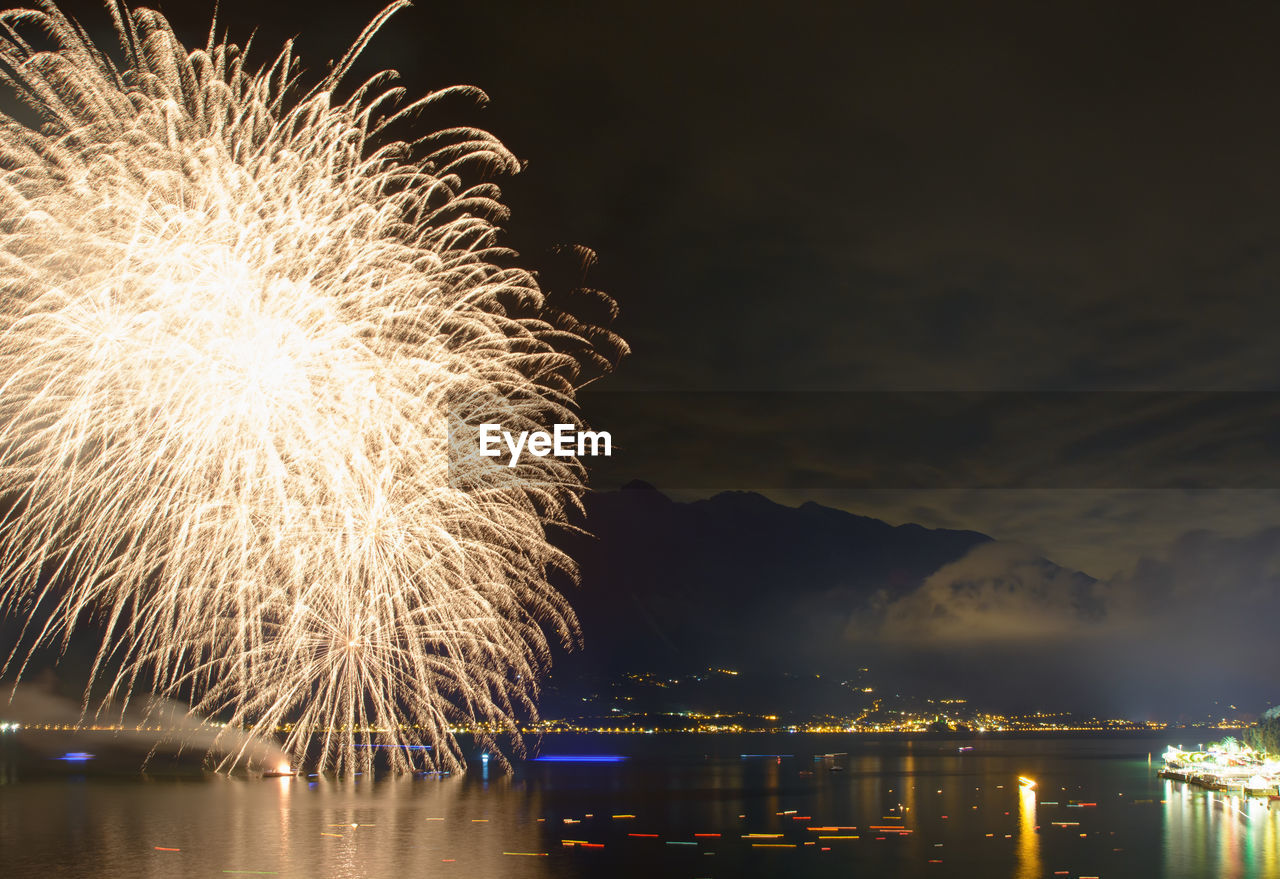 illuminated, night, water, firework, motion, architecture, nature, celebration, sky, glowing, reflection, long exposure, arts culture and entertainment, built structure, firework display, event, city, building exterior, no people, light, outdoors, sparks, firework - man made object