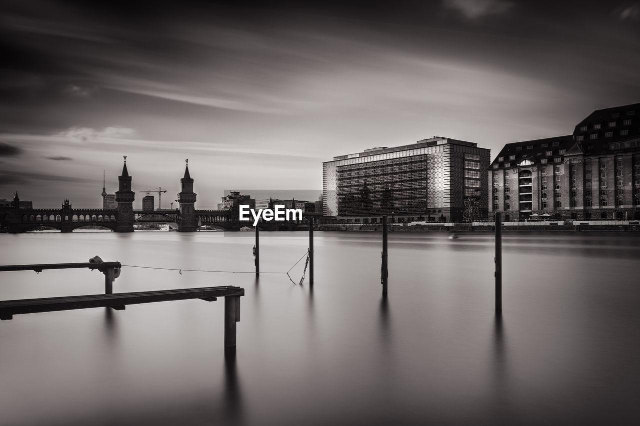 City Buildings By Riverside Against Sky