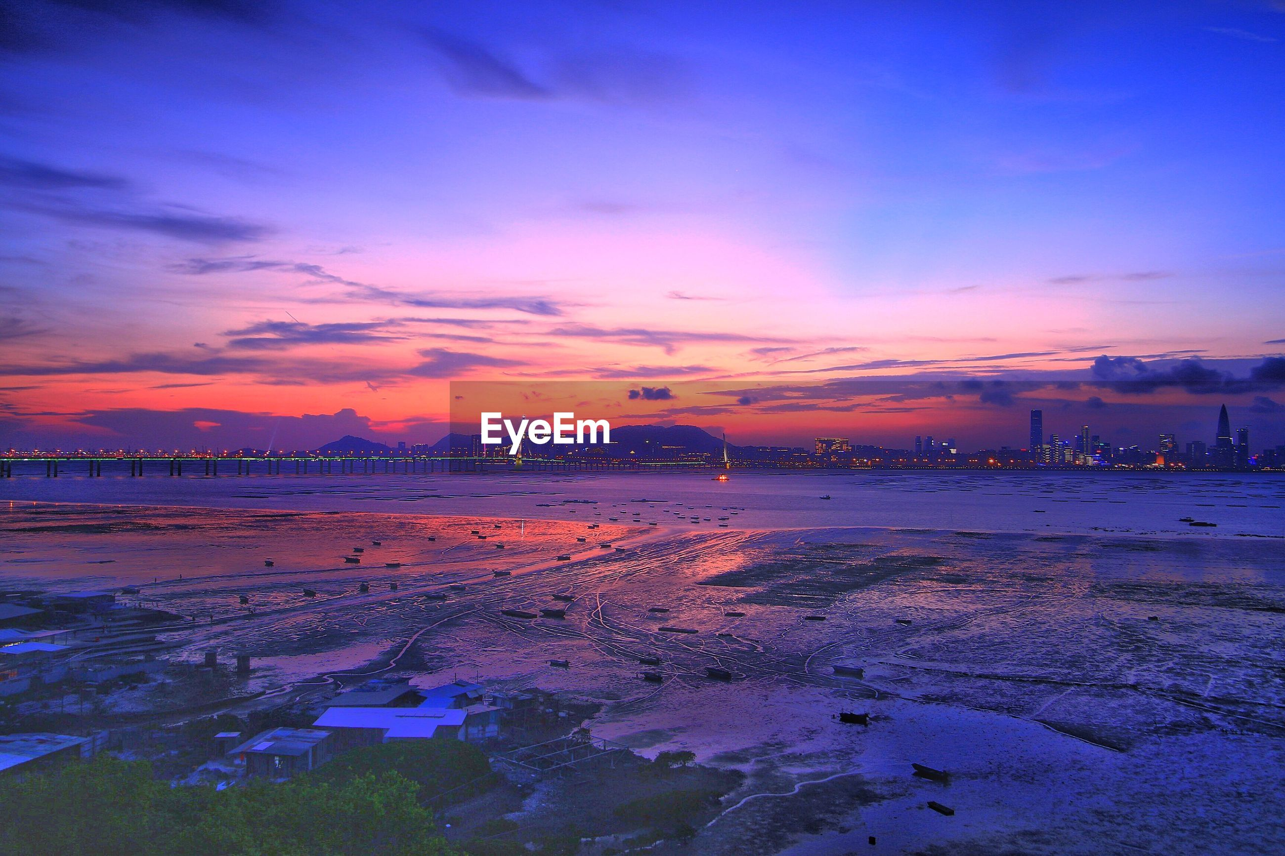 Scenic view of sea and city against romantic sky at sunset
