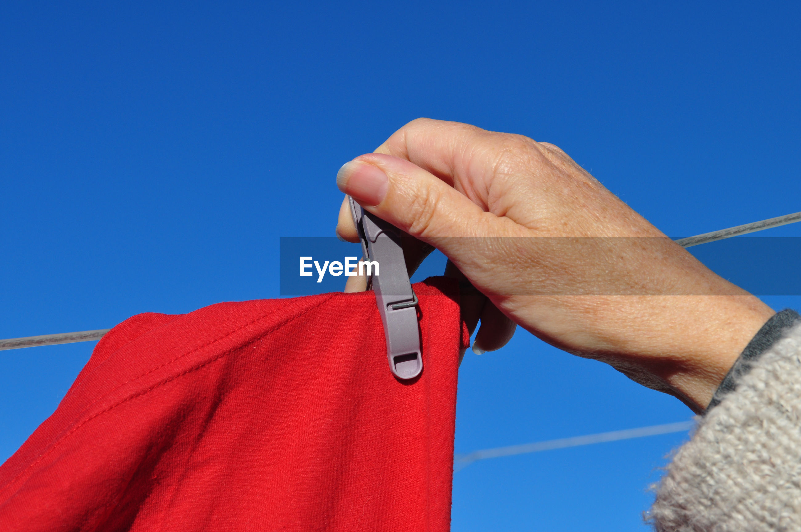 LOW ANGLE VIEW OF HAND HOLDING RED AGAINST CLEAR BLUE SKY