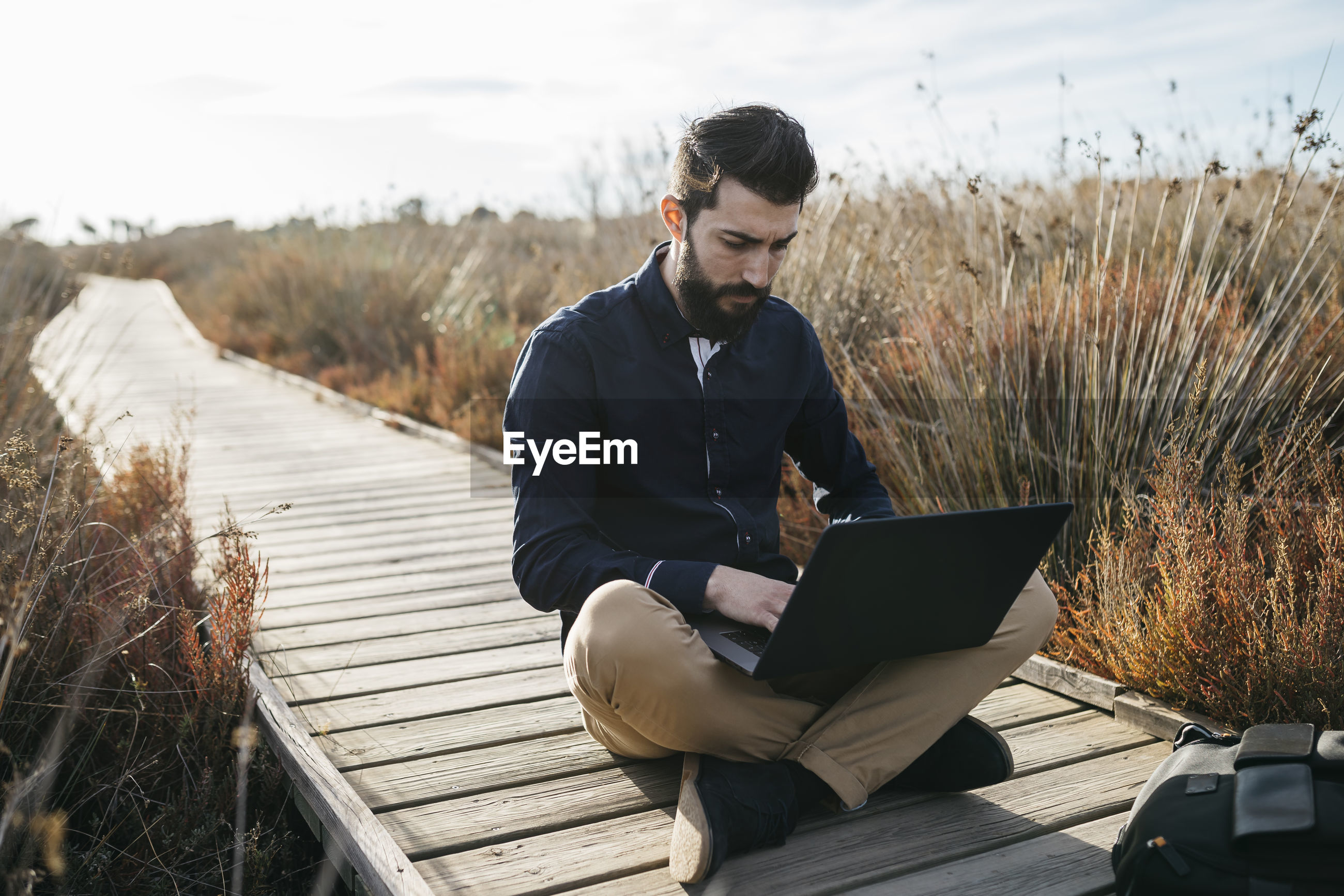 Man using laptop while sitting on boardwalk against sky