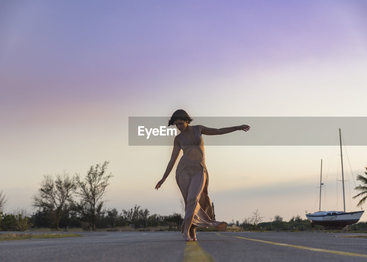 sky, full length, one person, real people, road, transportation, lifestyles, sunset, young adult, nature, leisure activity, standing, side view, young women, casual clothing, women, human arm, copy space, clear sky, outdoors, arms raised, leg
