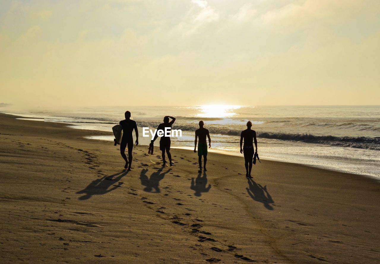 beach, land, sea, sky, horizon over water, horizon, water, sand, scenics - nature, group of people, beauty in nature, sunset, real people, nature, leisure activity, togetherness, men, lifestyles, sport, outdoors