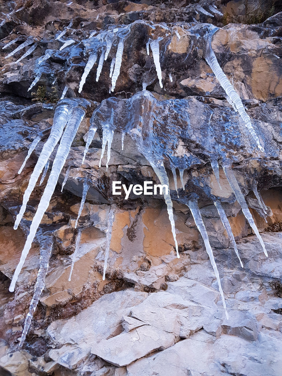 rock - object, ice, low angle view, cold temperature, water, day, icicle, frozen, outdoors, no people, nature, close-up