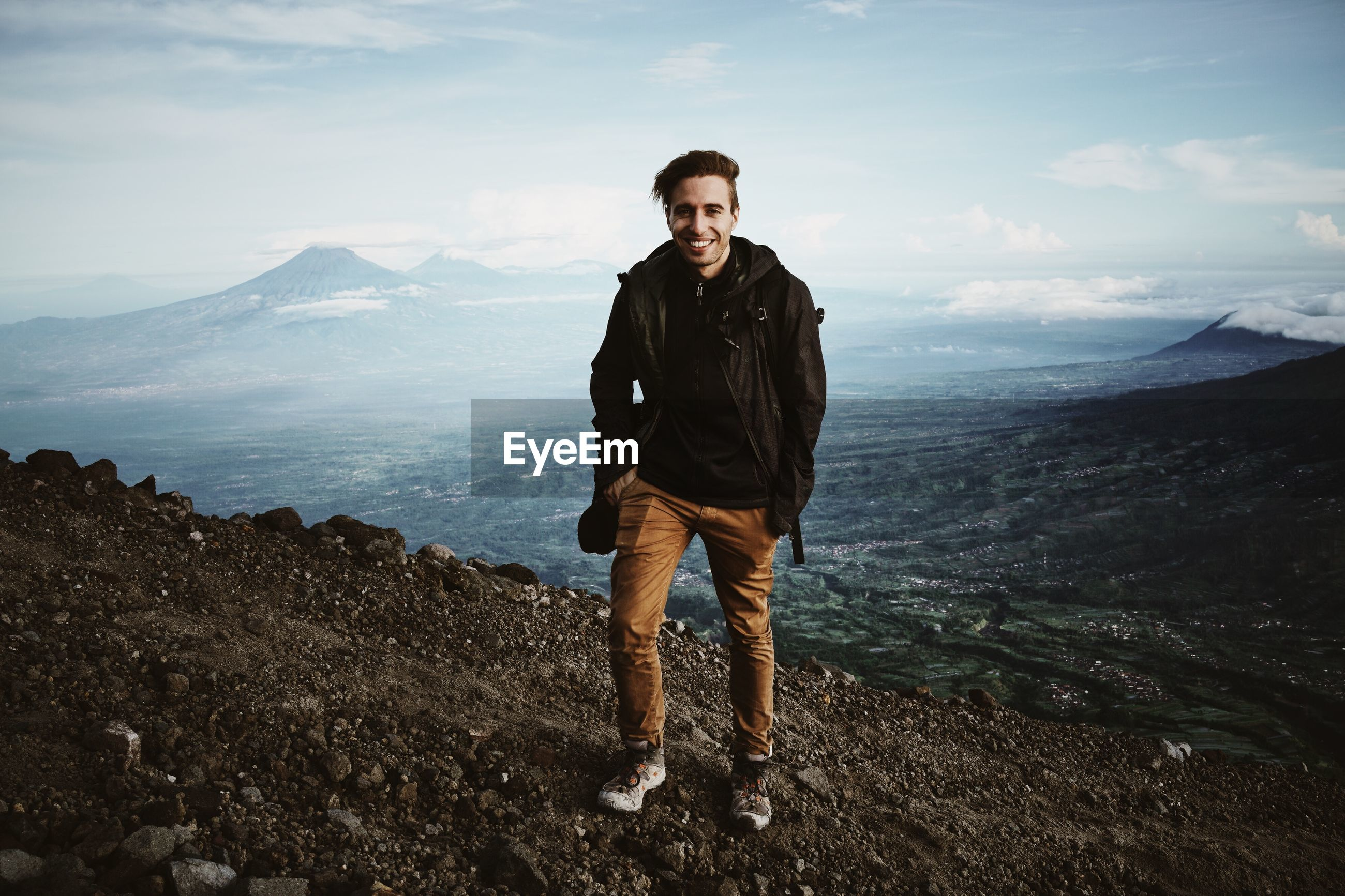 Portrait of young man hiking on mountain against sky