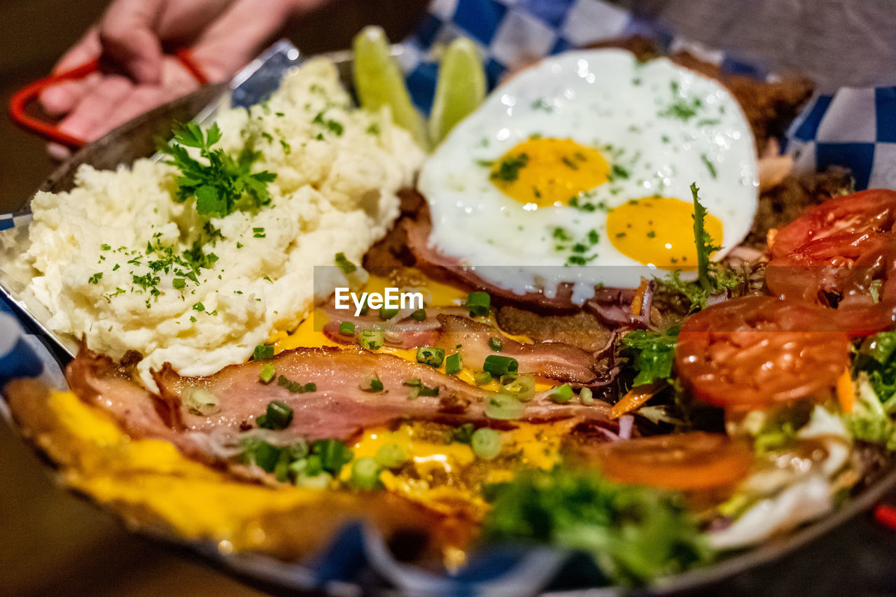 food and drink, food, ready-to-eat, freshness, egg, healthy eating, indoors, meal, close-up, plate, selective focus, serving size, wellbeing, table, still life, fried egg, meat, indulgence, egg yolk, breakfast, hand, temptation, herb, garnish, sunny side up