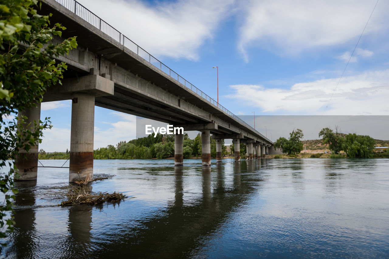 bridge, water, bridge - man made structure, built structure, architecture, connection, sky, architectural column, cloud - sky, nature, river, day, no people, transportation, reflection, waterfront, plant, tree, low angle view, outdoors