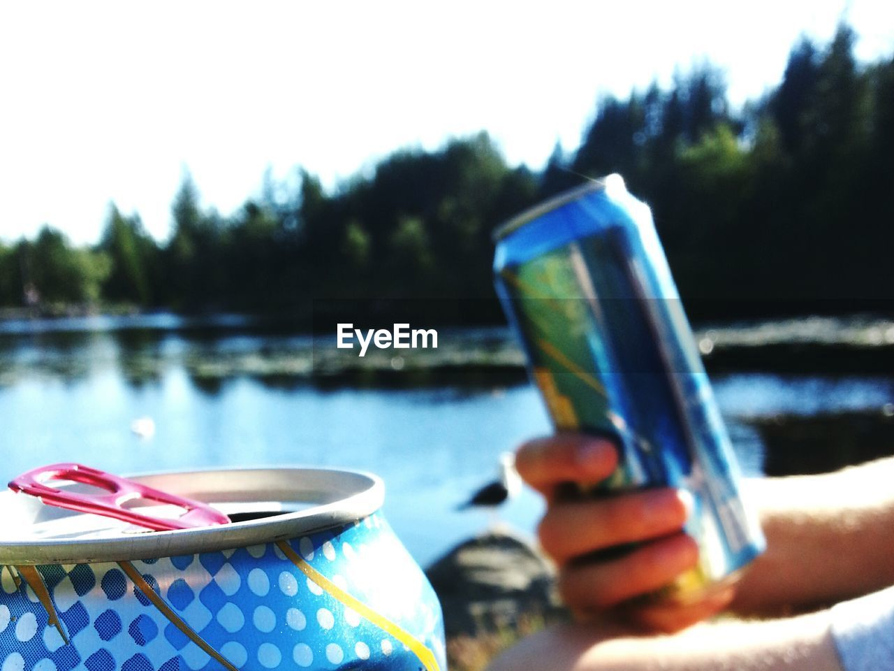 Close-Up Of Hand Holding Beer By River Against Sky
