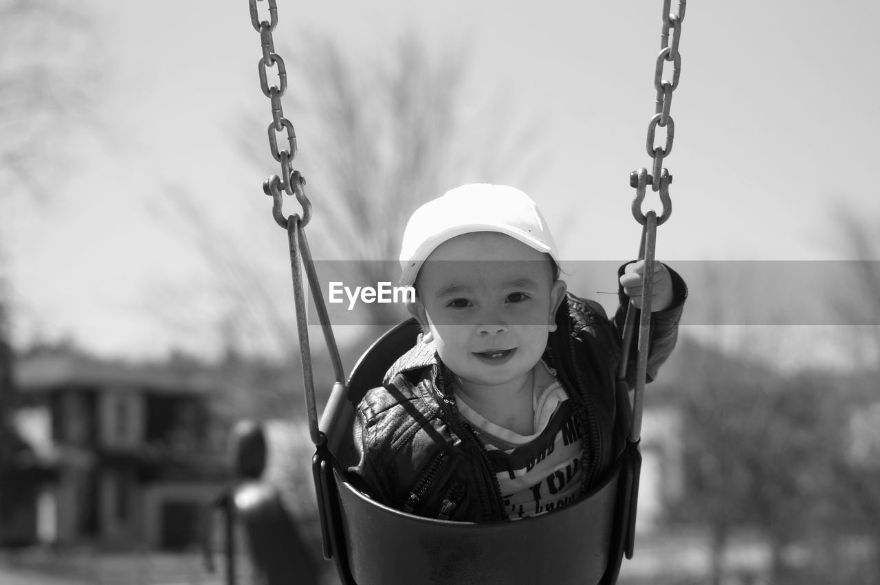 Portrait Of Cute Baby Boy Swinging At Playground