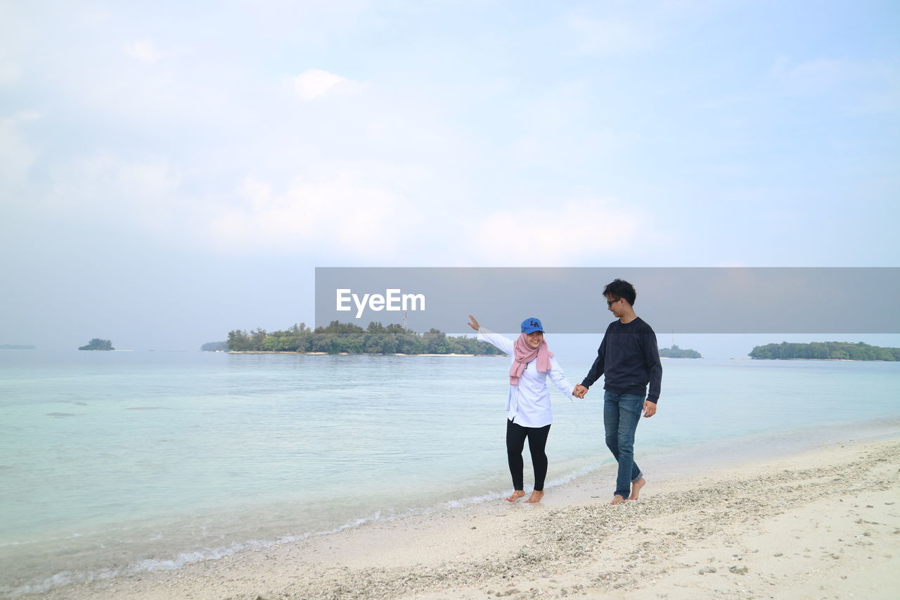Full length of young couple holding hands while walking on shore at beach against sky