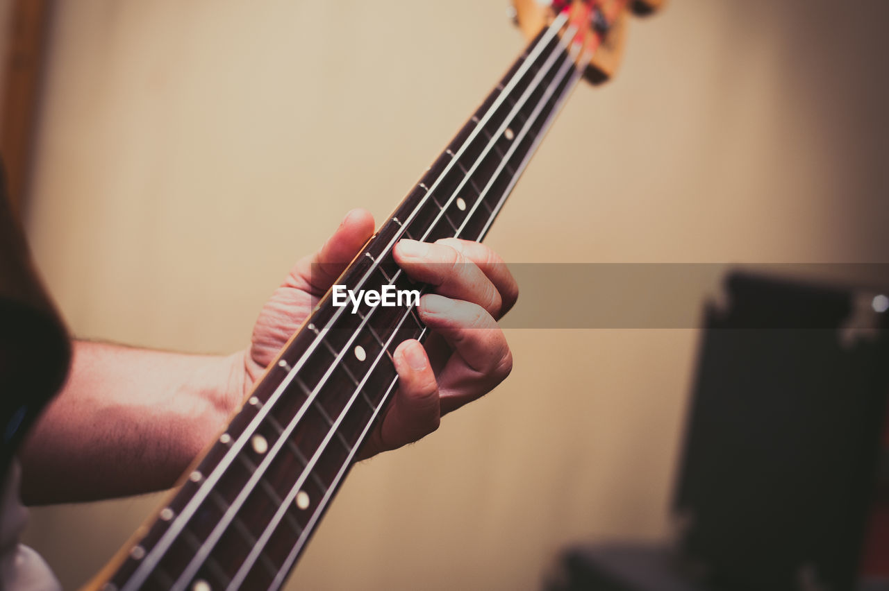 Cropped hands of man playing bass guitar