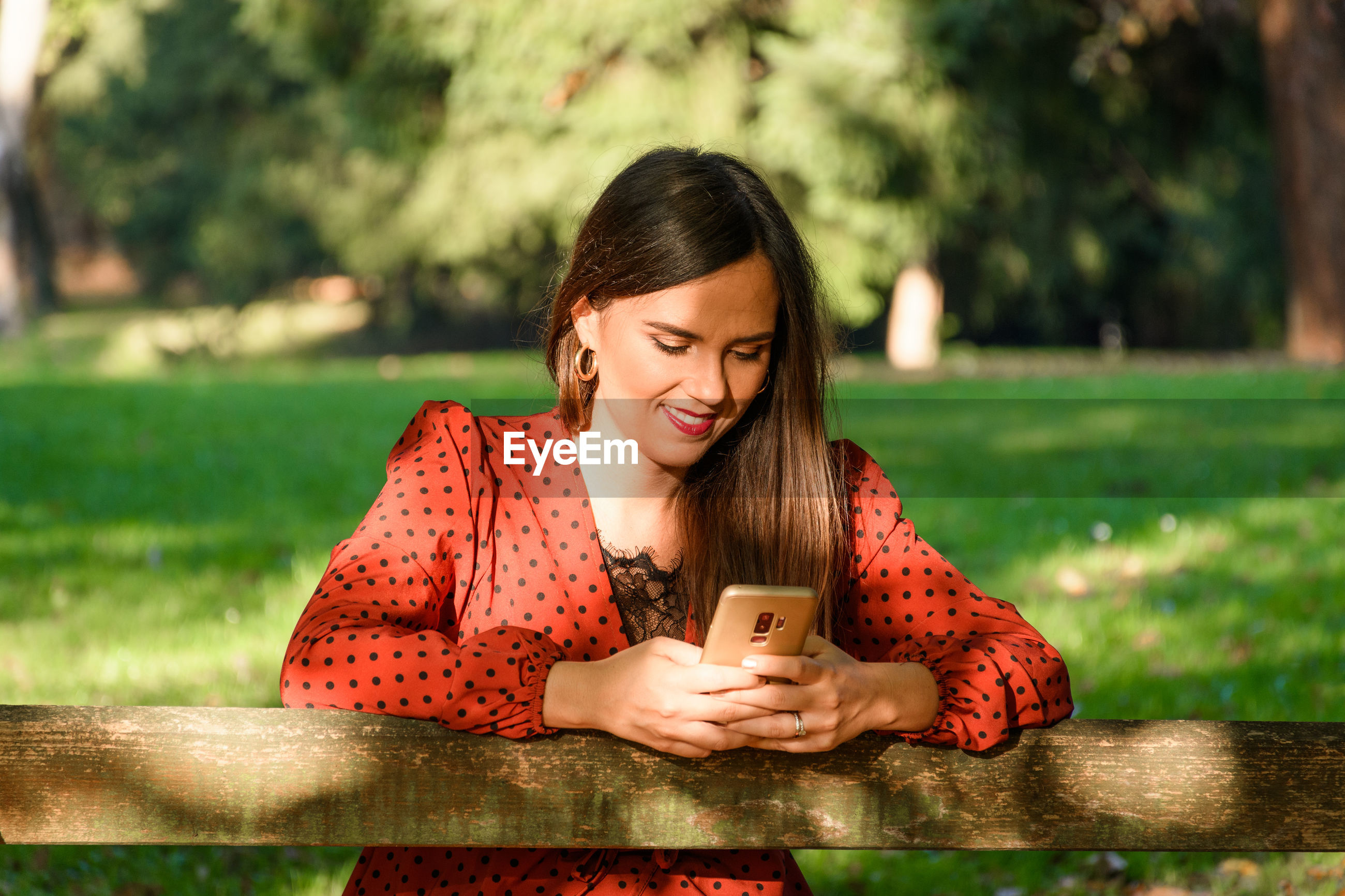 Happy smiling young woman using her mobile phone.