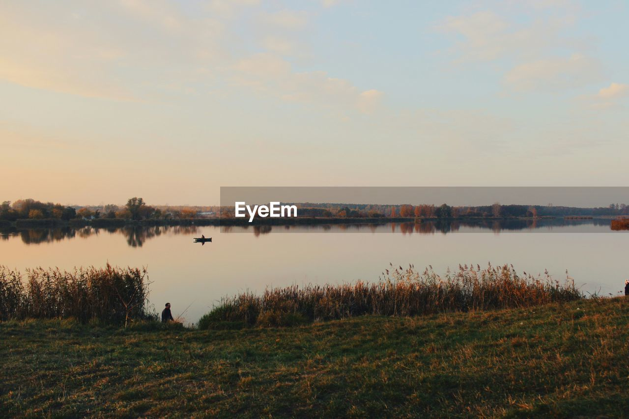 Scenic View Of Lake Against Cloudy Sky At Autumn