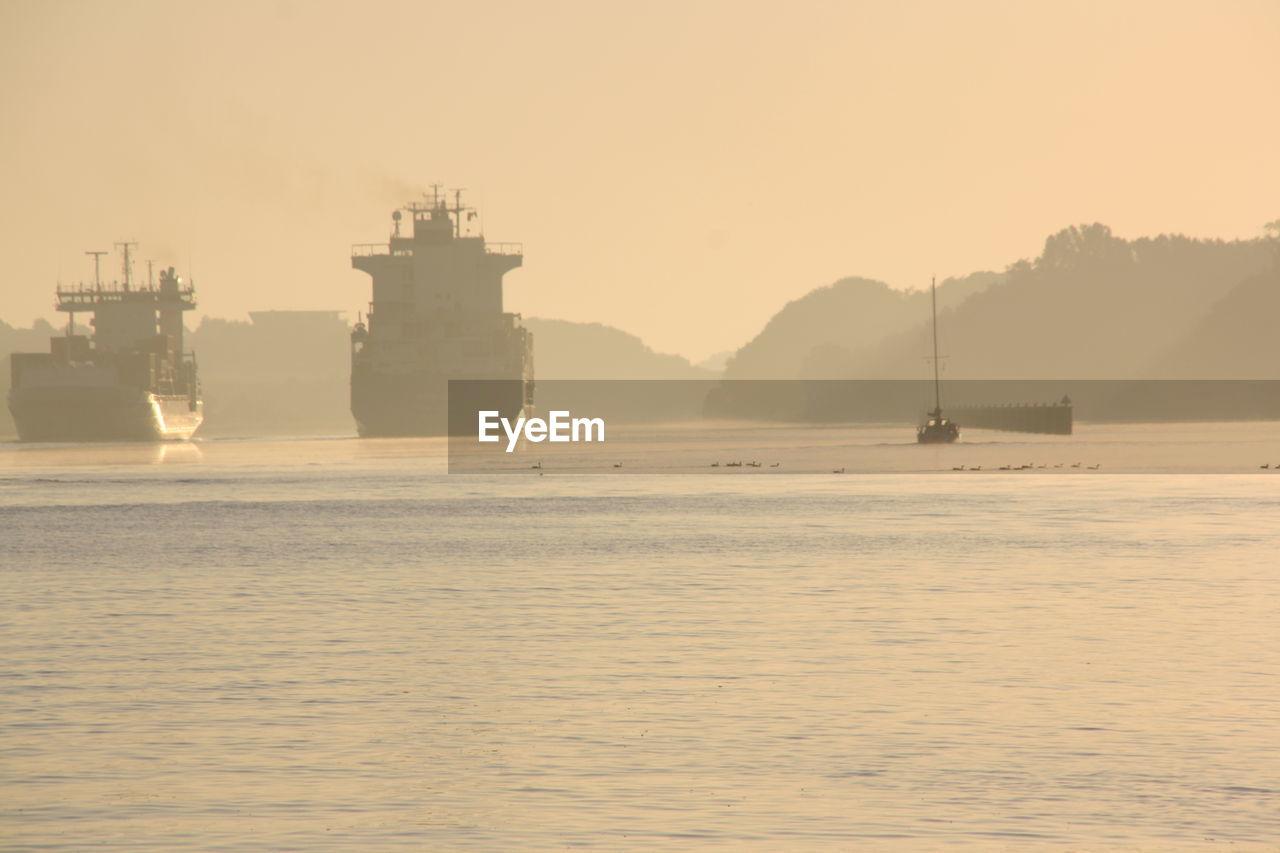 Boats in sea at sunrise