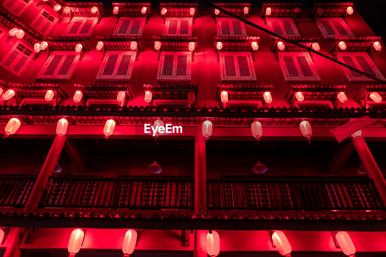 red, no people, architecture, illuminated, built structure, low angle view, full frame, building exterior, lighting equipment, technology, night, large group of objects, building, backgrounds, pink color, communication, pattern, outdoors, close-up