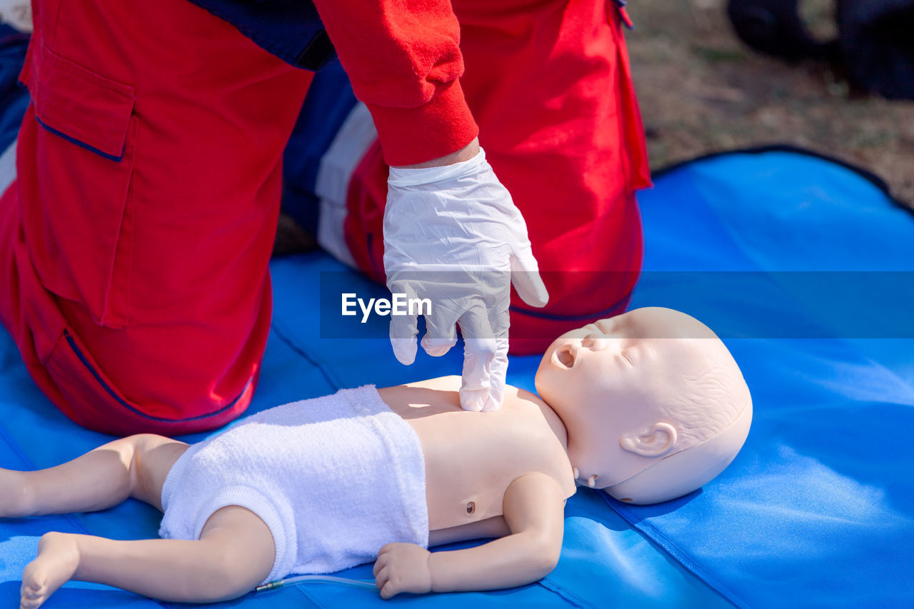 Midsection of person practicing cpr on dummy outdoors