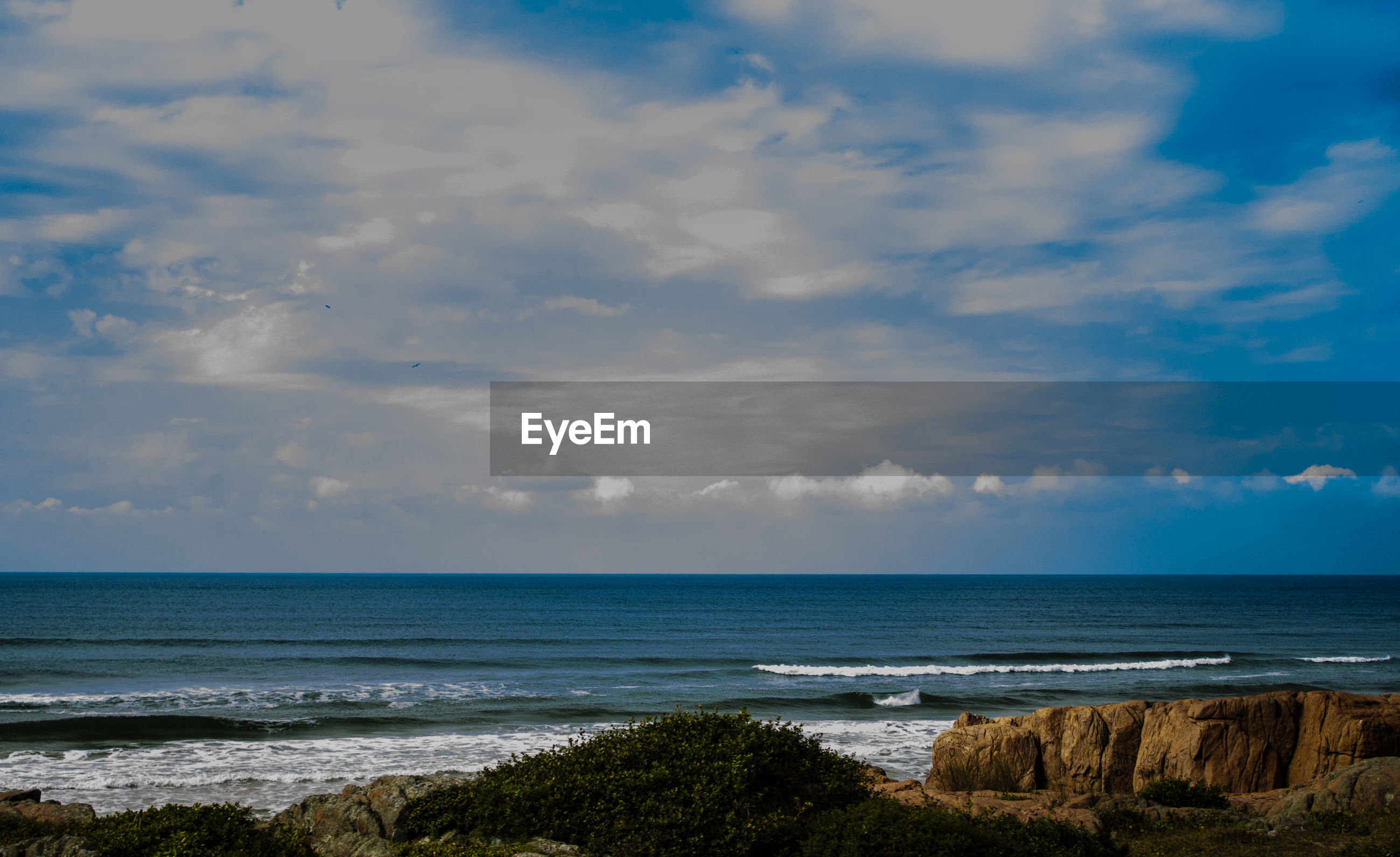 SCENIC VIEW OF SEA AND MOUNTAIN AGAINST CLOUDY SKY