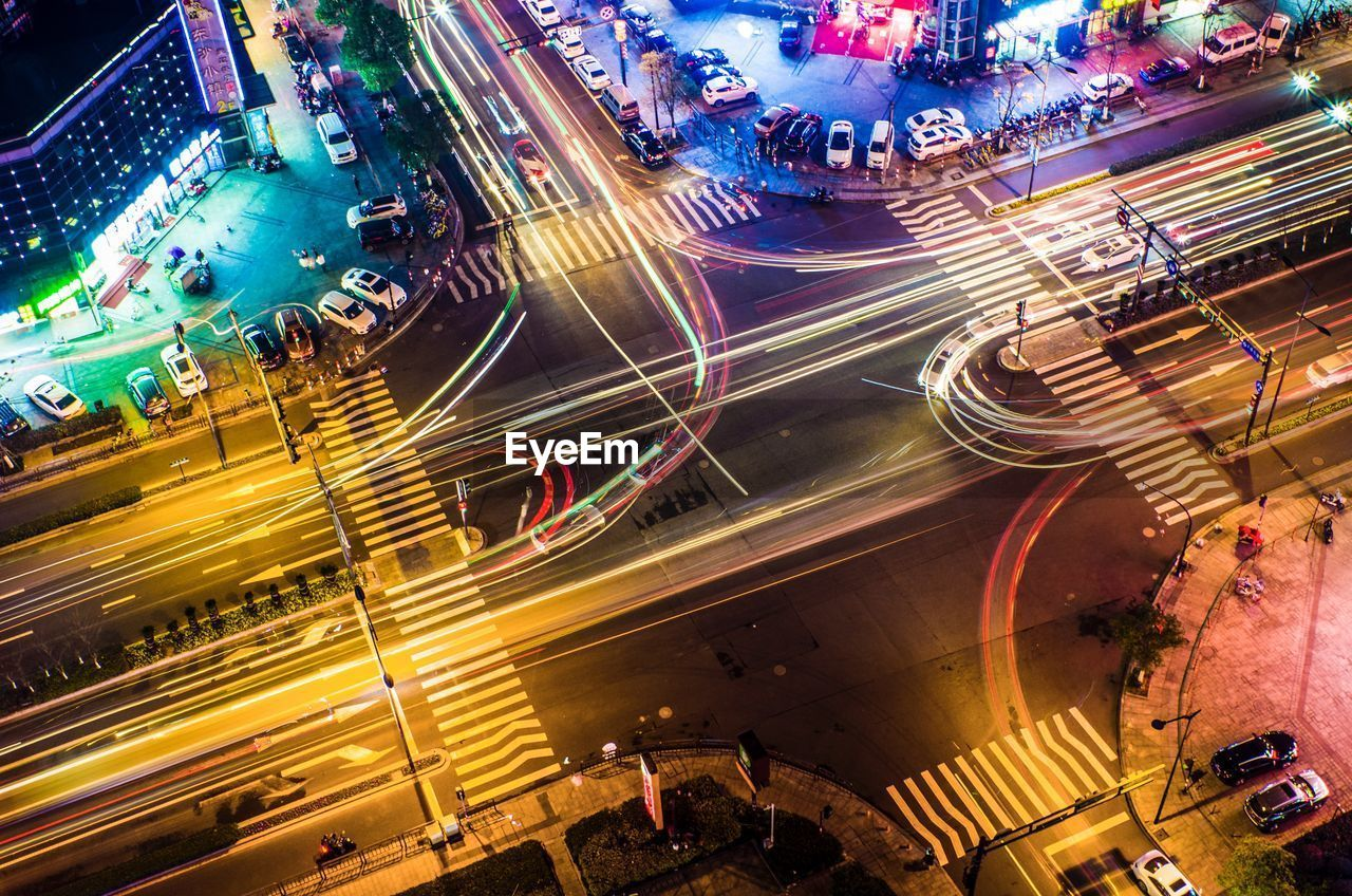 traffic, high angle view, transportation, night, motion, long exposure, city, light trail, speed, city life, road, illuminated, street, city street, blurred motion, rush hour, aerial view, crowded, architecture, car, street light, road intersection, outdoors, land vehicle, building exterior, cityscape, high street, people
