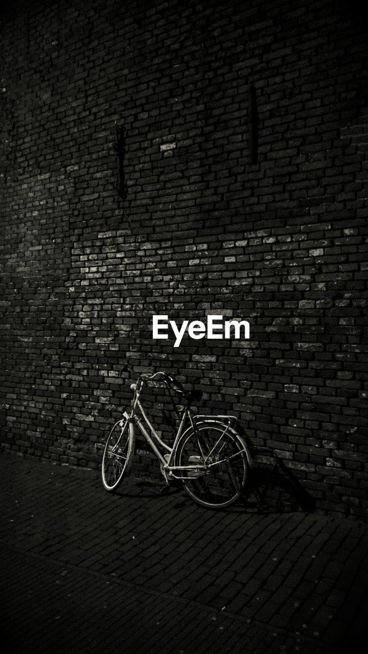 Bicycle leaning on brick wall